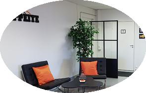 Toimiston aula yritysväreillä. Mustat huonekalut, joita piristetty yrityksen brändivärillä: oranssilla.
